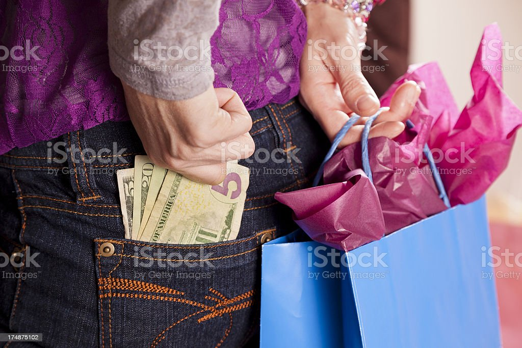 Consumerism. Woman with money in pocket and holding shopping bag royalty-free stock photo