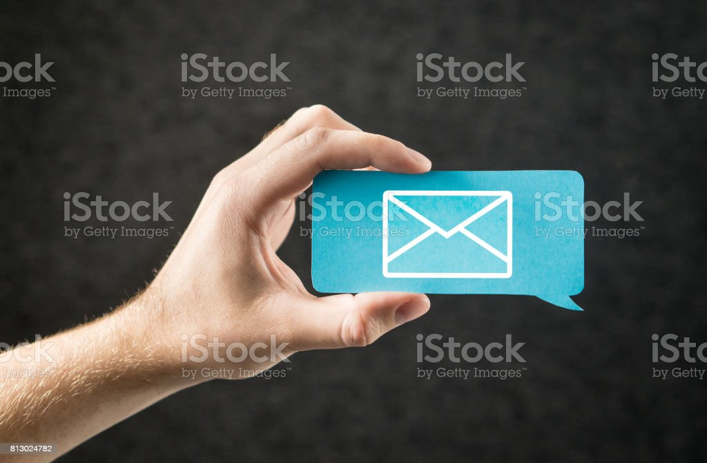 Contact us, send email and message banner for business website. Customer service and subscribe newsletter. Hand holding cardboard paper speech bubble and chat balloon with letter envelope icon. stock photo