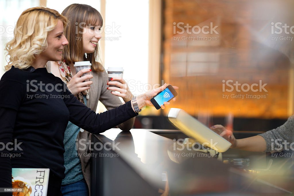 Contactless payment  with mobile phone at the coffee bar stock photo
