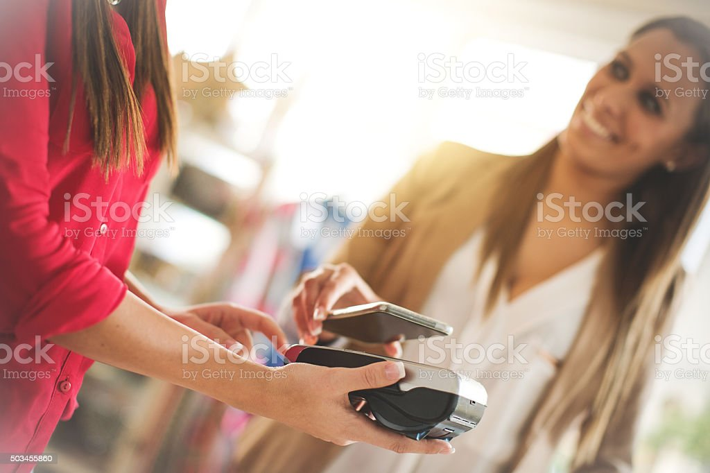 Contactless Payment with Mobile Phone in a shop stock photo