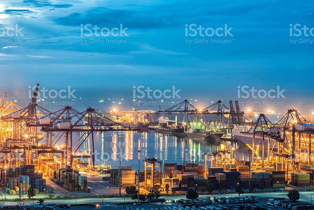 Container Cargo freight ship with working crane bridge in port stock photo