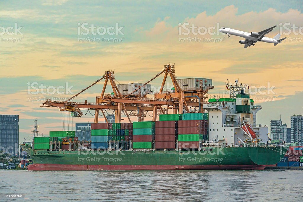 Container Cargo freight ship with working crane loading bridge i stock photo