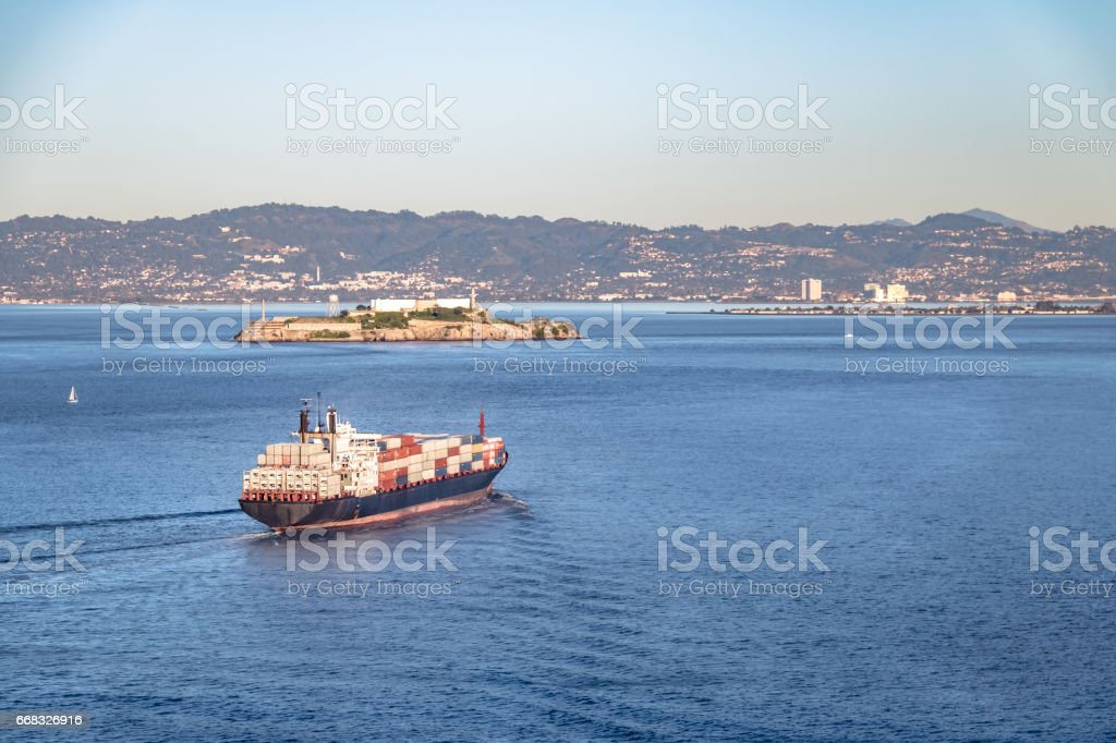 Container Cargo Ship entering San Francisco Bay and Alcatraz Island - San Francisco, California, USA stock photo