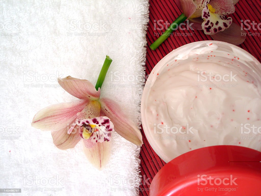 container of cosmetic cream with pink orchids and towel royalty-free stock photo