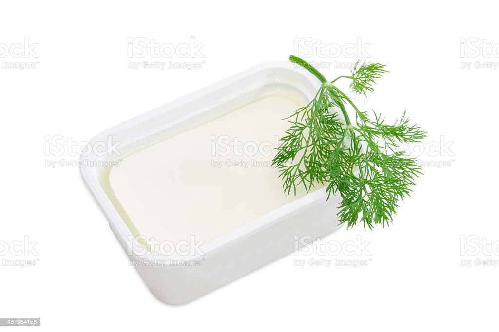 Container of feta cheese and a branch of a dill stock photo