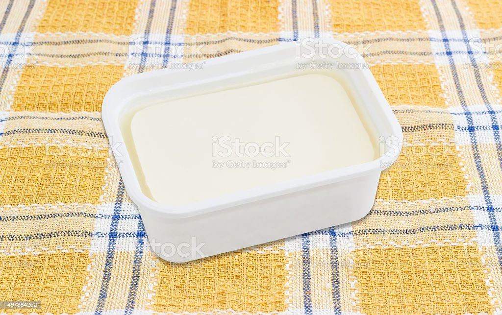 Container of feta cheese on a checkered tablecloth stock photo
