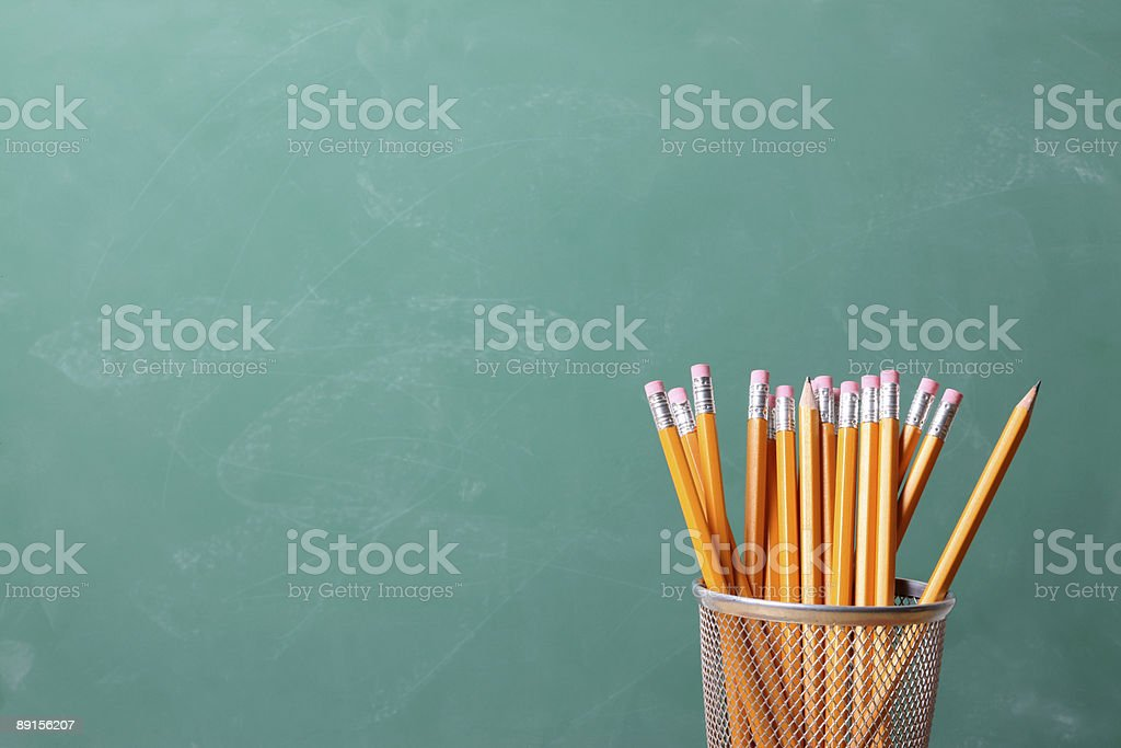 Container of new pencils with clean chalkboard background stock photo