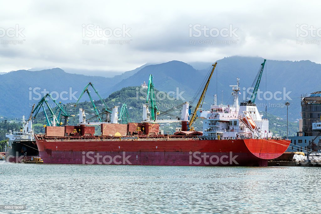 Container ship and fishing boat in the seaport stock photo