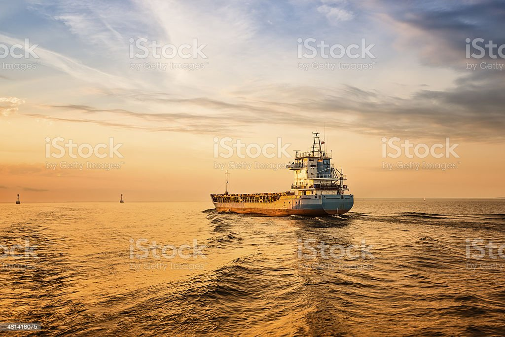 Container ship on sea road on sunset. stock photo
