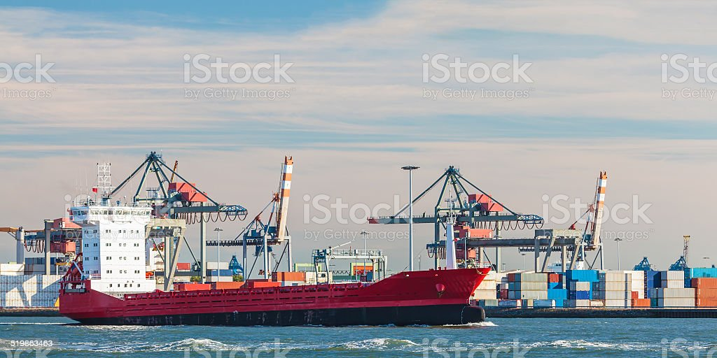 Container ship passing cranes in Rotterdam harbor stock photo