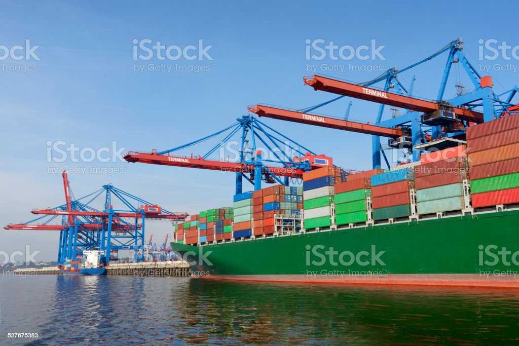 Container ship under gantry cranes and blue sky in harbor stock photo