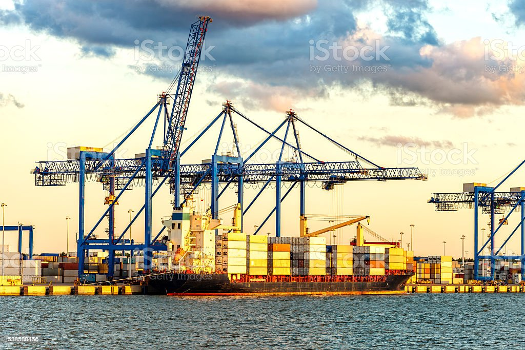 Container ship unloading at a dock stock photo