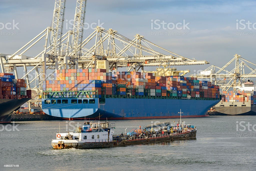 Container ships and bunker fuel barge in port stock photo