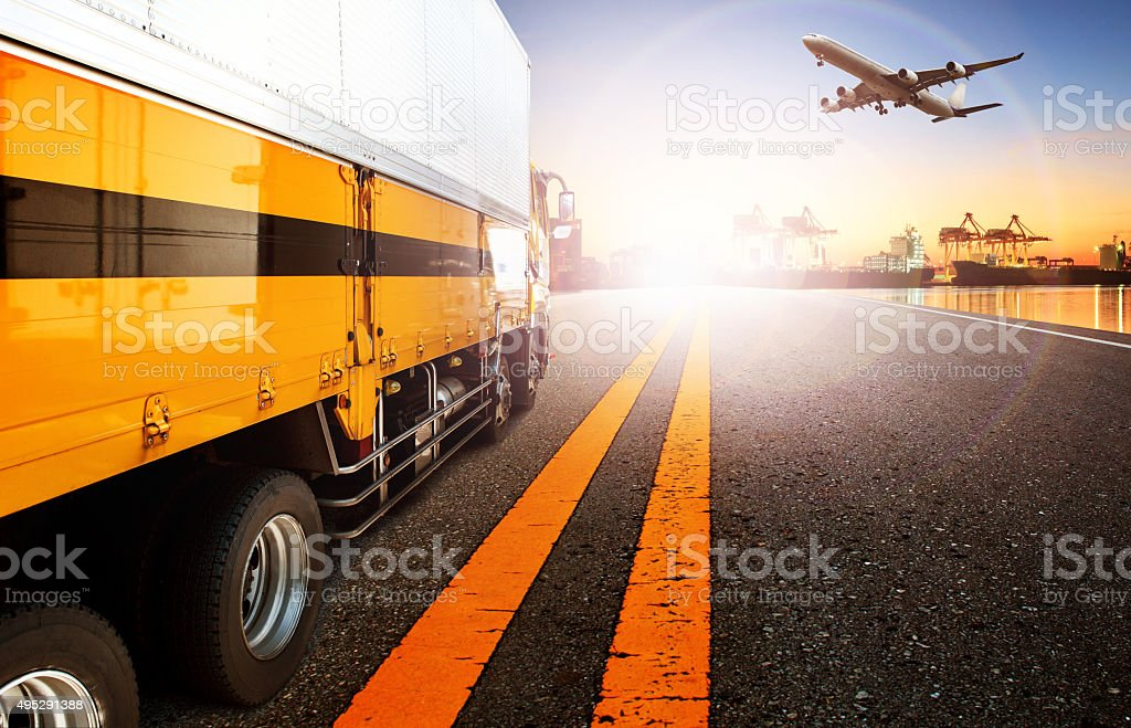 container truck in ship port and cargo plane flying stock photo