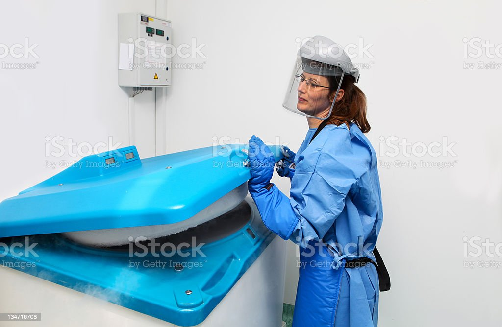 Container with liquid nitrogen...doctor in hazmat suit at work royalty-free stock photo