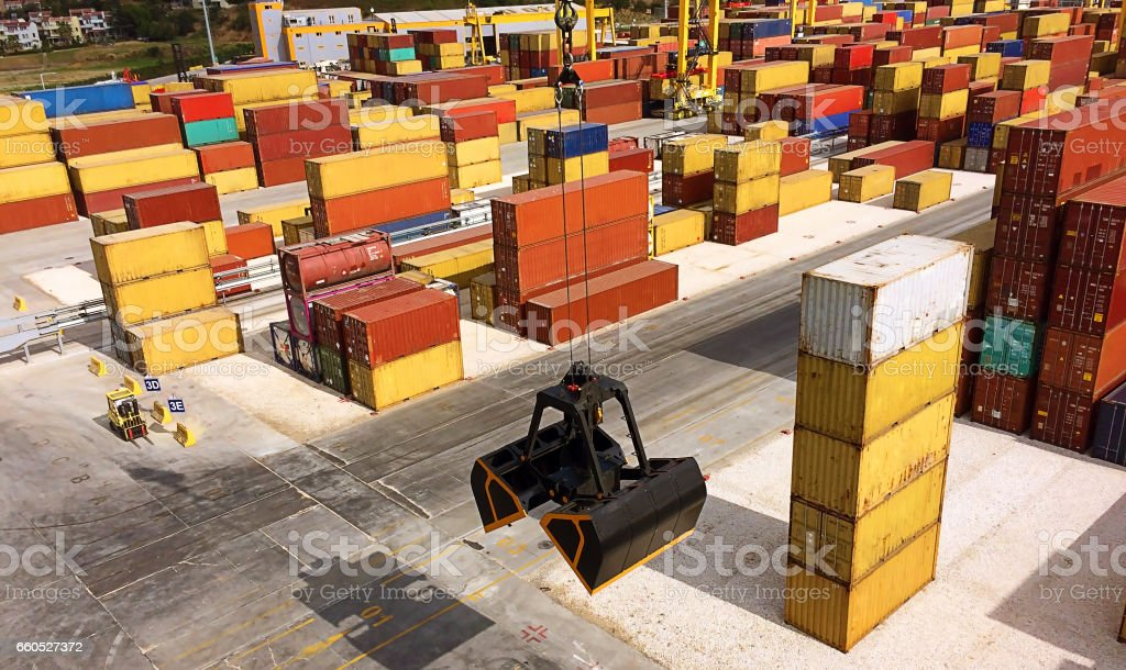 containers at the port and mechanical hydraulic grabber on the crane stock photo
