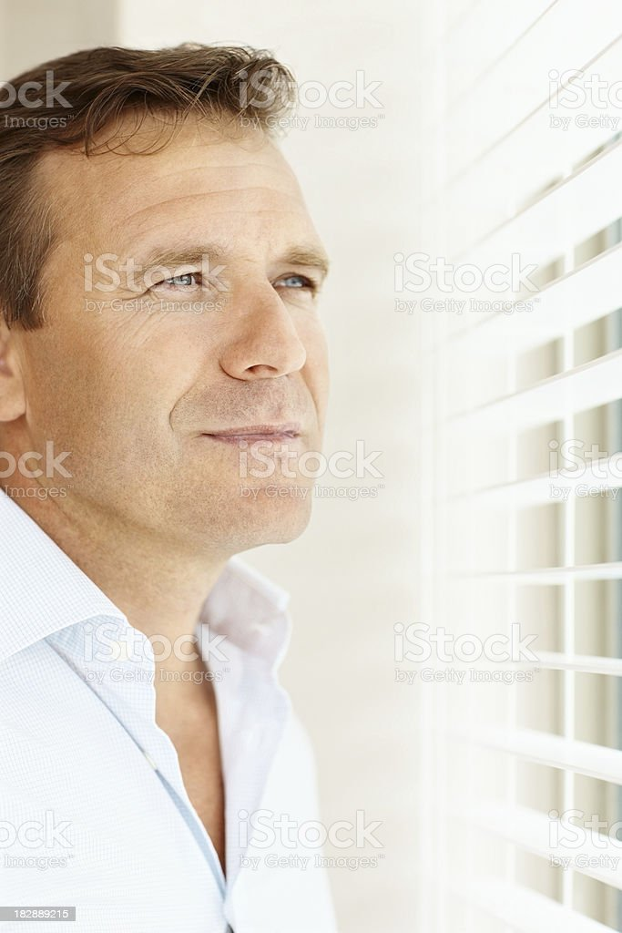Contempaltive mature man looking through blinds royalty-free stock photo