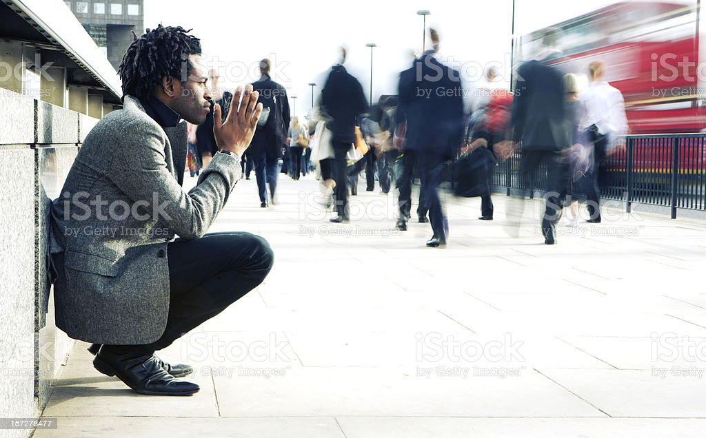 Contemplation from a solitary character contrasting against a hurried world stock photo