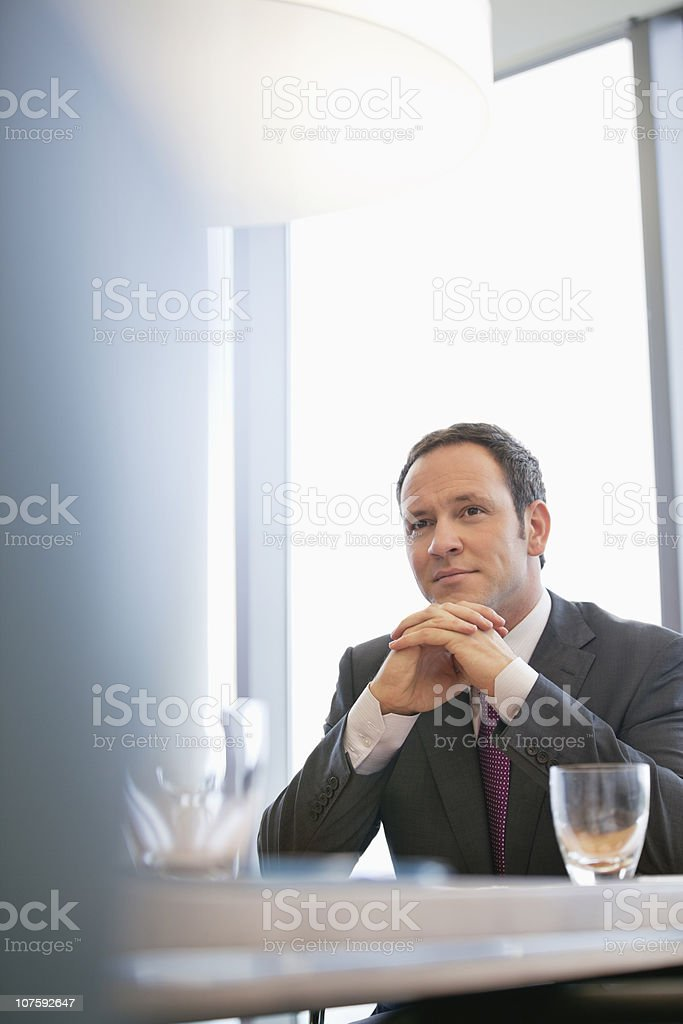 Contemplative businessman sitting at conference table royalty-free stock photo