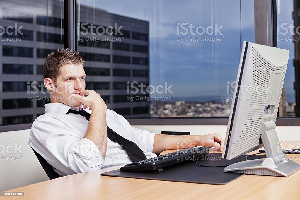 Contemplative Businessman Sitting at Desk stock photo