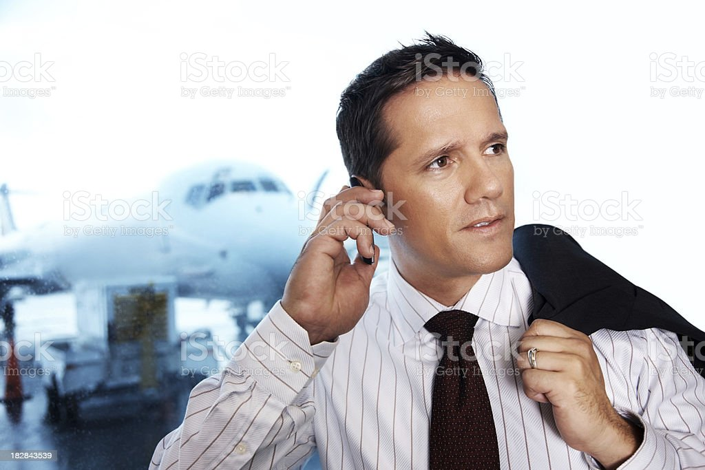 Contemplative businessman talking over cellphone with aeroplane in the background royalty-free stock photo