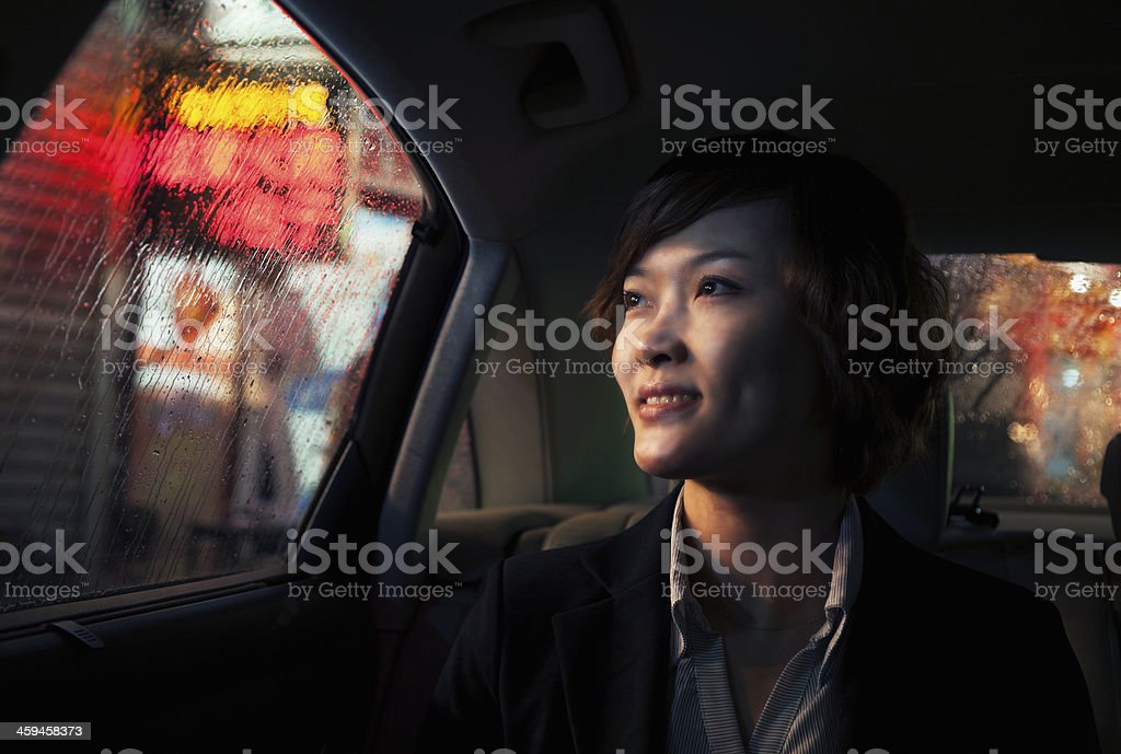 Contemplative Businesswoman looking out of car window through the rain stock photo