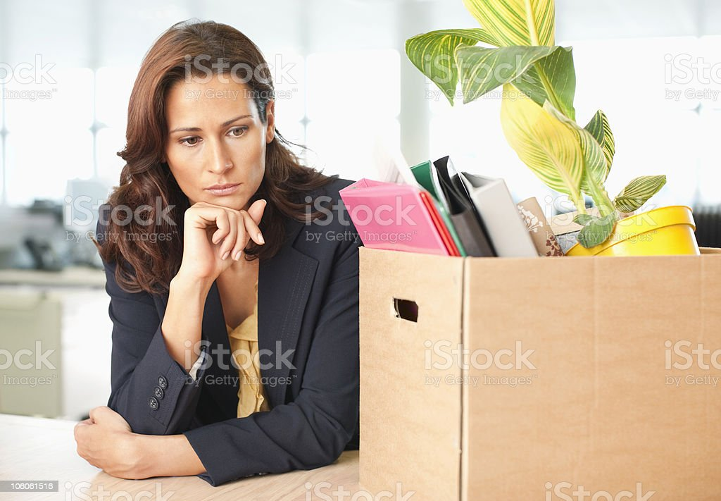 Contemplative businesswoman with office supply in cardboard box royalty-free stock photo