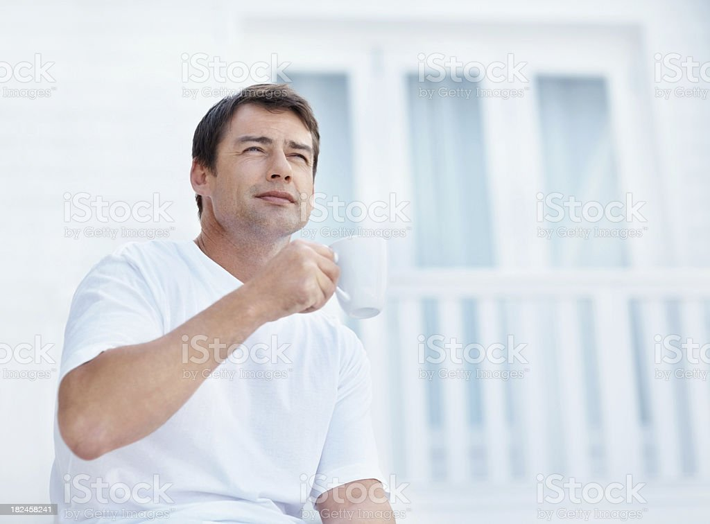 Contemplative mature guy holding a coffee cup royalty-free stock photo
