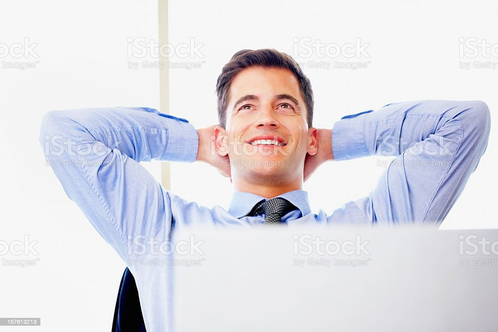 Contemplative mid adult businessman relaxing at work royalty-free stock photo