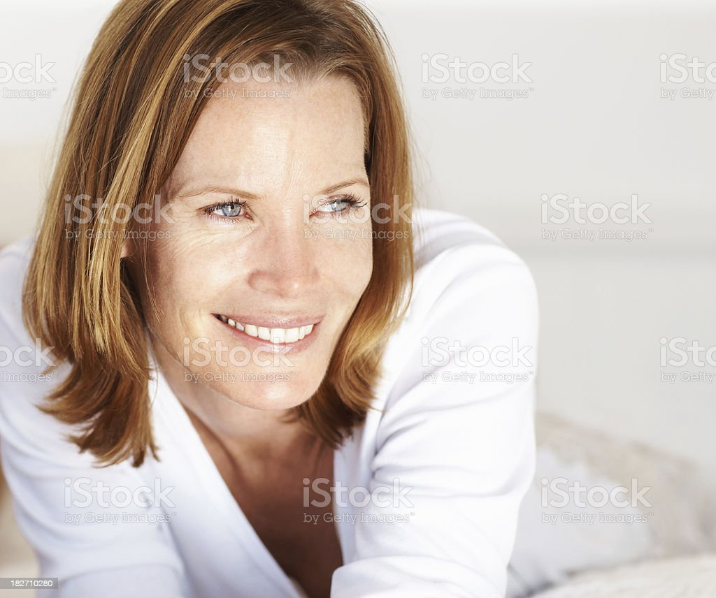 Contemplative mid adult lady lying on bed royalty-free stock photo