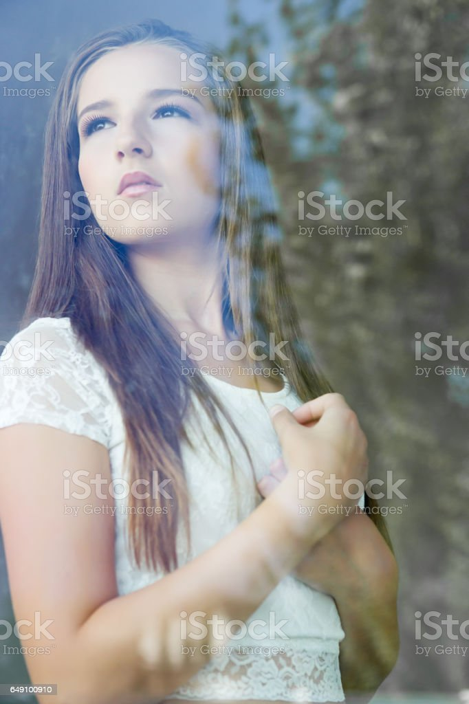 Contemplative woman looking through glass window stock photo
