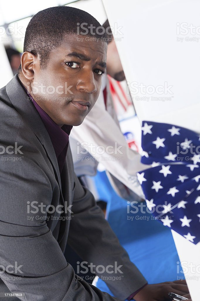 Contemplative young man choosing a candidate at voting election center royalty-free stock photo