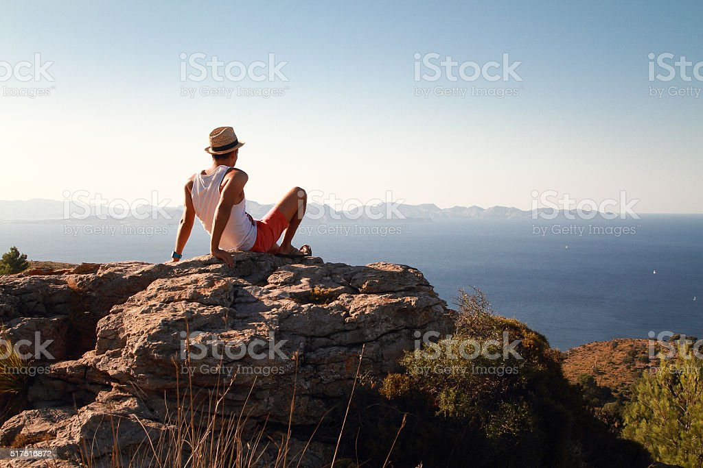 Contemplative young man sitting on the top of a mountain stock photo