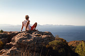 Contemplative young man sitting on the top of a mountain