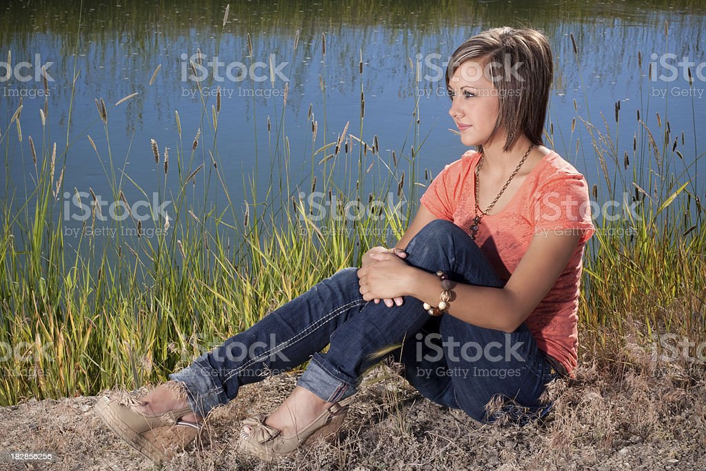 Contemplative Young Woman by Water stock photo