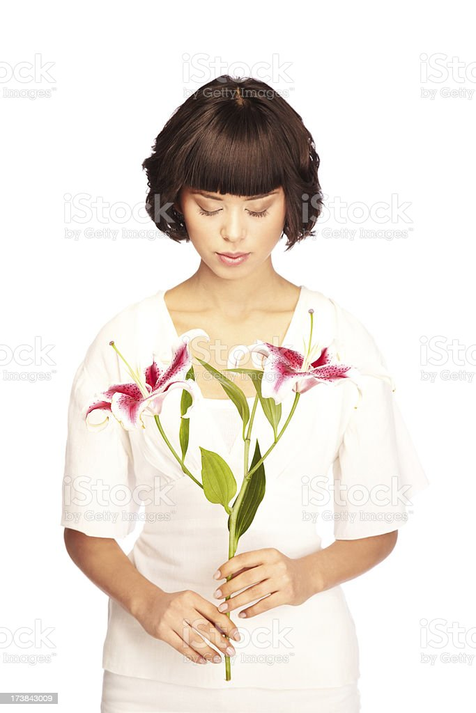 Contemplative Young Woman Looking Down at Flowers stock photo