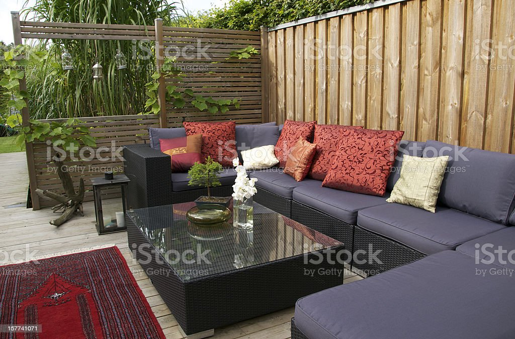 Contemporary patio with large wicker sofa. Garden design royalty-free stock photo