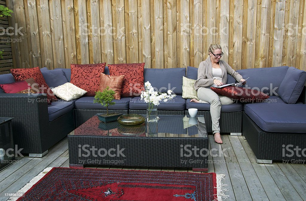 Contemporary Patio with large wicker sofa. Woman reading stock photo