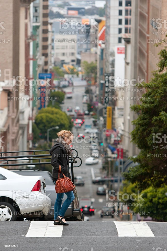 Contemporary Scene Of San Francisco As Woman Crosses Hilly Street stock photo