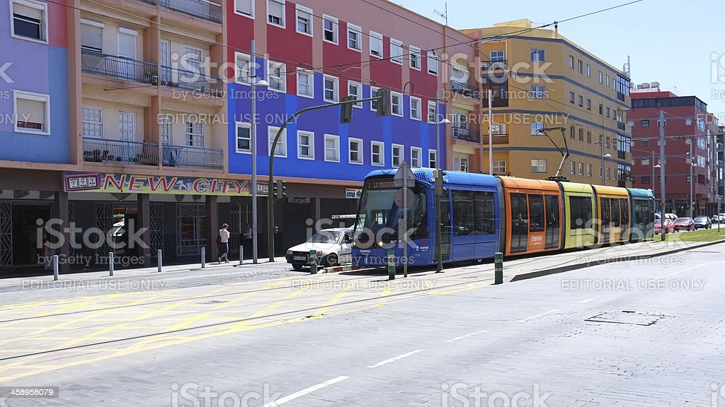 Contemporary train in a Spanish city with colorful buildings royalty-free stock photo