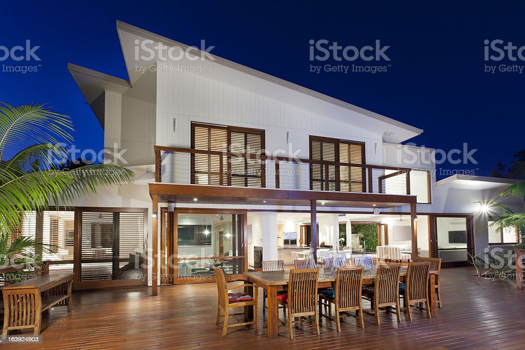 Contemporary two story home with deck at dusk stock photo