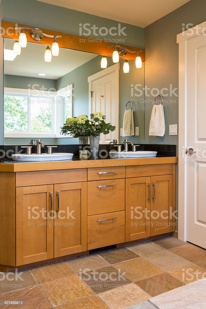 Contemporary upscale bathroom interior with wood cabinets and tile floor stock photo