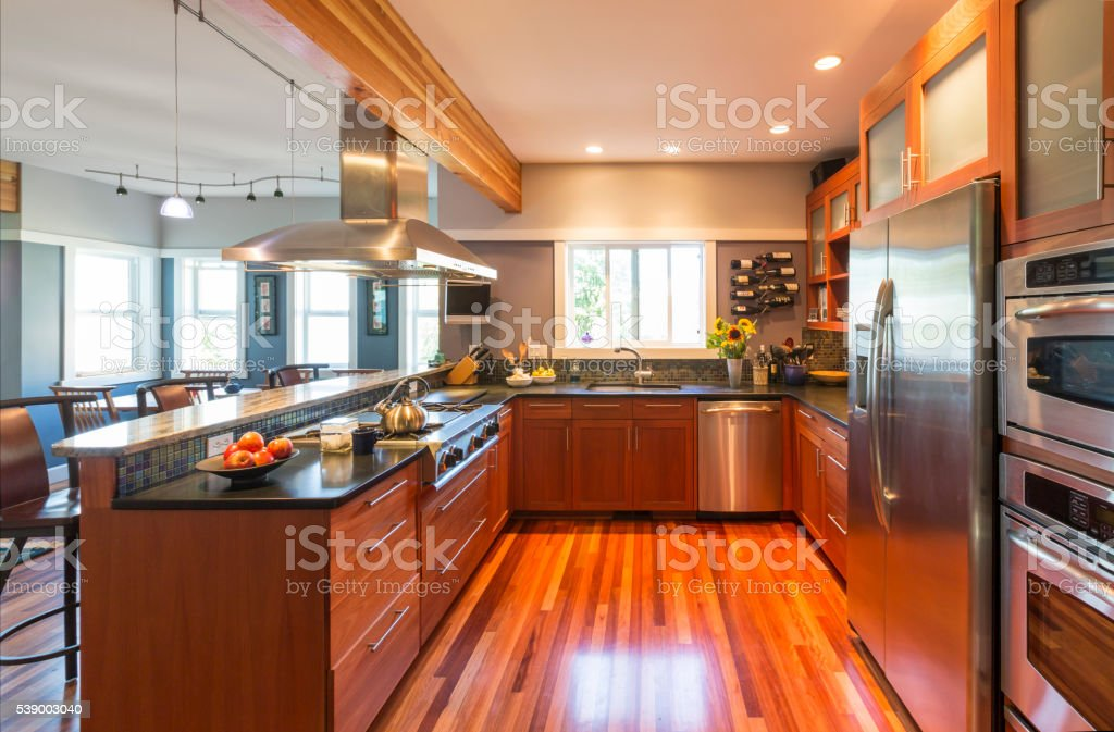 Contemporary upscale home kitchen interior with wood cabinets and floors stock photo