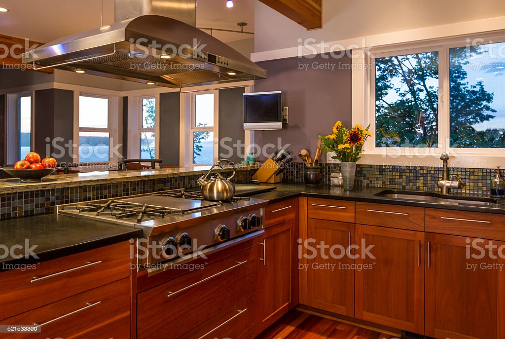 Contemporary upscale home kitchen with wood cabinets and quality appliances stock photo