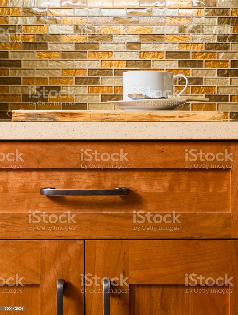 Contemporary upscale kitchen interior with wood cabinets and glass tile stock photo