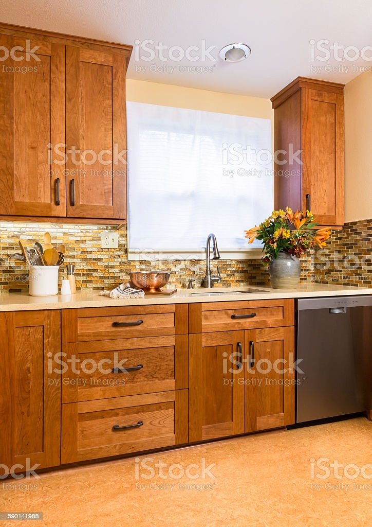 Contemporary upscale kitchen with wood cabinets and glass tile detail stock photo