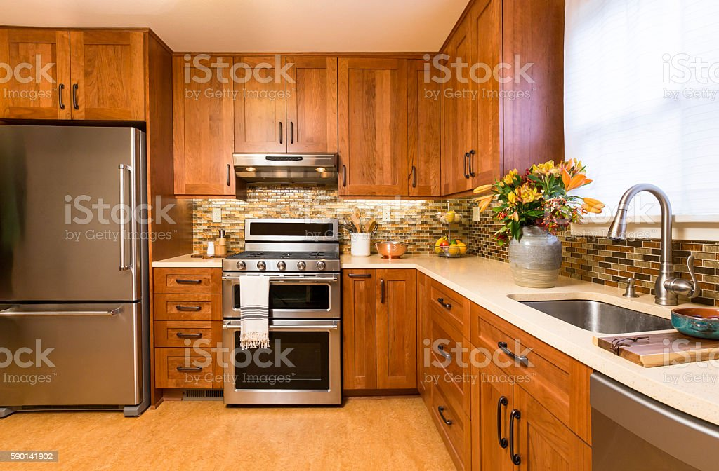 Contemporary upscale kitchen with wood cabinets and stainless steel appliances stock photo