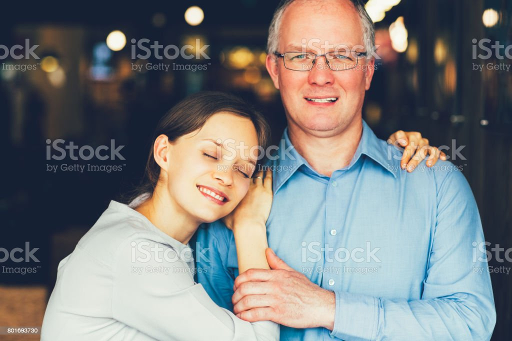 Content Adult Woman Embracing Middle-aged Father stock photo