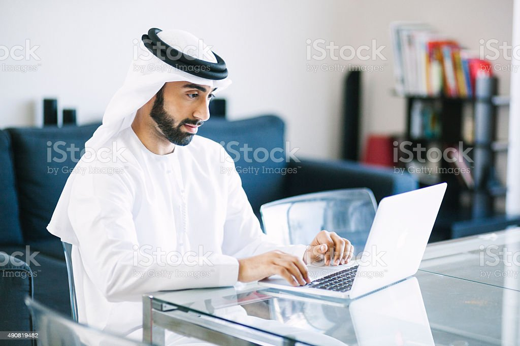 Content Arab Man Using Laptop at Home stock photo