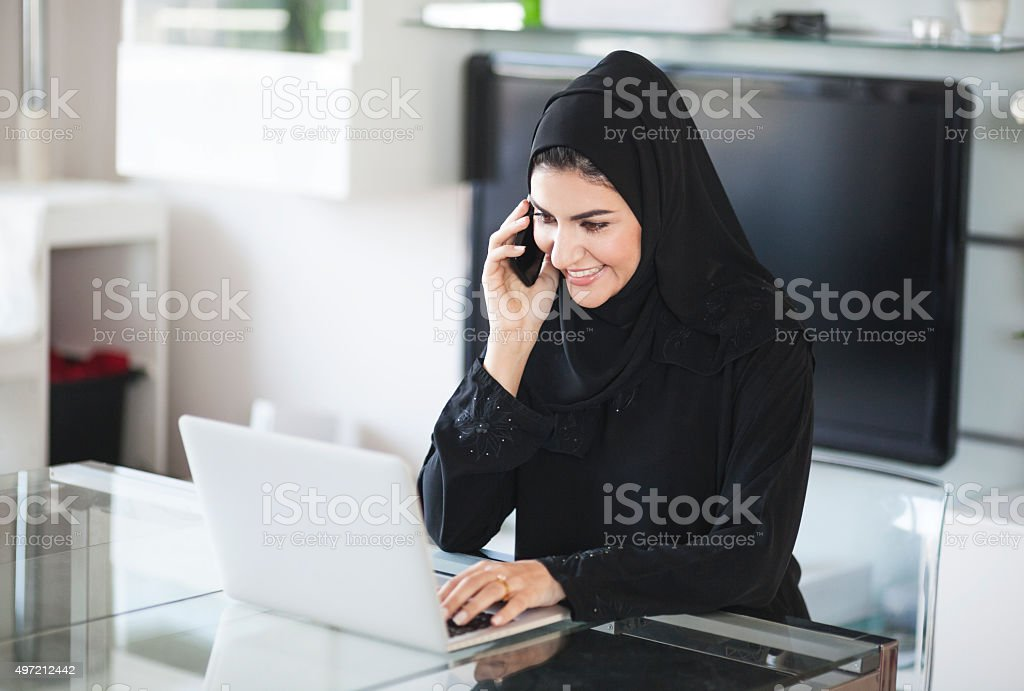 Content Arab Woman Working At Home Using Smartphone and Laptop stock photo
